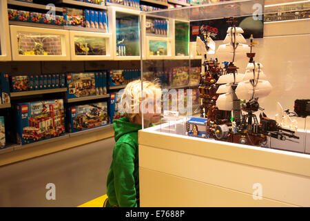 A boy looking at a display in the Lego Store on the shopping street Strøget in Copenhagen, Denmark - Stock Photo
