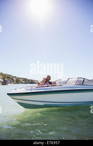 Couple laying together in boat on water - Stock Photo
