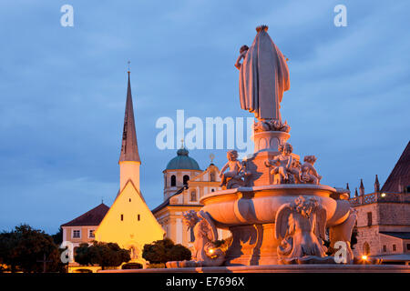 statue of Maria, church Magdalenakirche and the tower of the Chapel of Grace on Kapellplatz square in Altoetting - Stock Photo