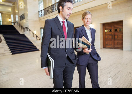 Lawyers walking through courthouse together - Stock Photo