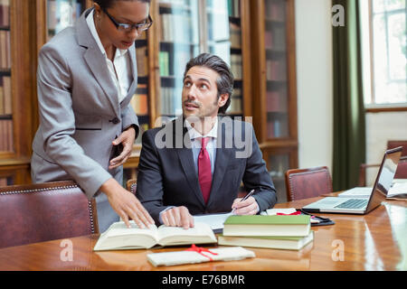 Lawyers doing research together in chambers - Stock Photo