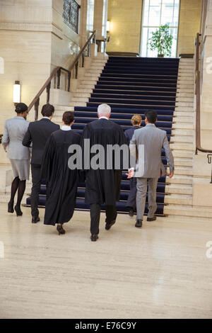 Judges and lawyers walking through courthouse together - Stock Photo