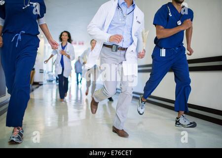 Doctors and nurses rushing in hospital hallway - Stock Photo