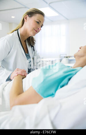 Doctor talking to patient in hospital room - Stock Photo