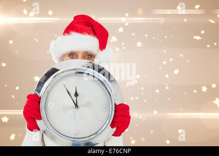 Composite image of festive woman holding clock - Stock Photo