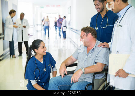 Doctor and nurses talking to patient in hospital - Stock Photo