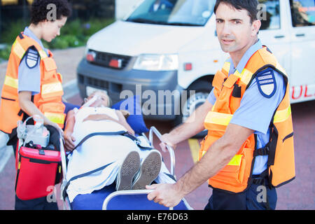 Paramedics wheeling patient on stretcher in hospital parking lot - Stock Photo