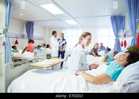 Doctors, nurses and patients in hospital room - Stock Photo