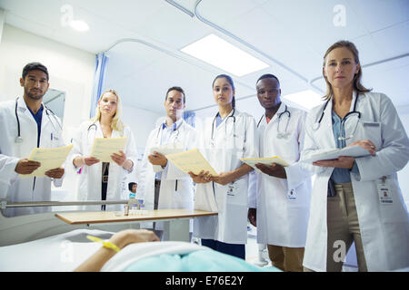 Doctor and residents examining patient in hospital bed - Stock Photo
