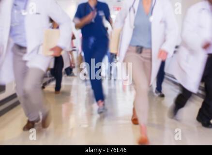 Doctors rushing in hospital hallway - Stock Photo