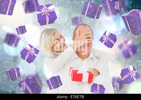 Composite image of woman surprising man with gift - Stock Photo