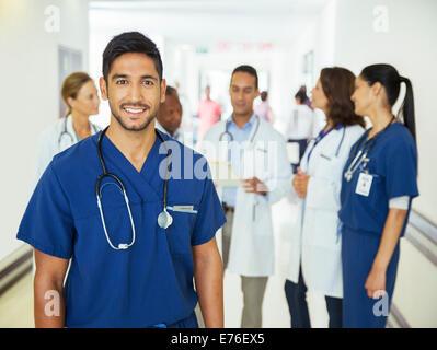 Nurse smiling in hospital hallway - Stock Photo