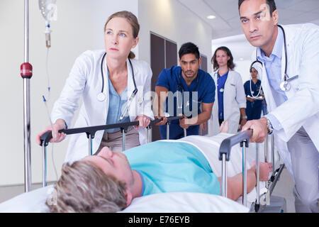 Doctors wheeling patient in hospital hallway - Stock Photo