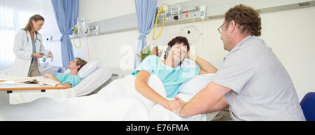Man talking to wife in hospital room - Stock Photo