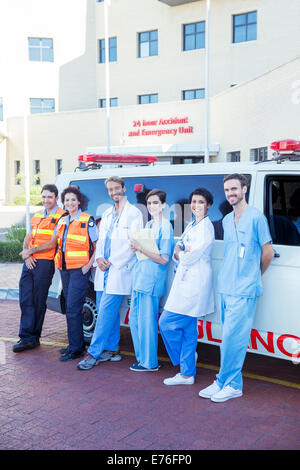 Doctors, nurses and paramedics smiling by ambulance - Stock Photo