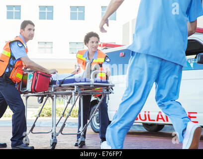 Paramedics wheeling patient in hospital parking lot - Stock Photo