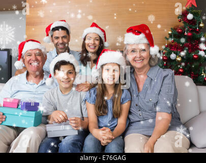 Composite image of extended family in christmas hats with gift boxes in living room - Stock Photo
