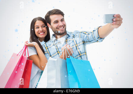 Composite image of attractive young couple with shopping bags taking a selfie - Stock Photo