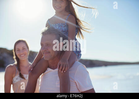 Father holding daughter on shoulders on beach - Stock Photo