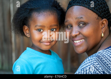 Face shot of little African girl with mom outdoors. - Stock Photo