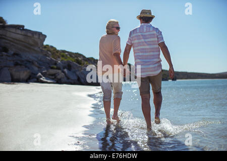Couple holding hands walking along shore - Stock Photo