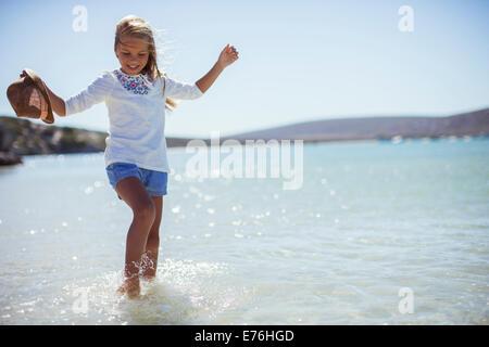 Young girl splashing in water on beach - Stock Photo