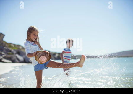 Young girl splashing in water on beach - Stock Photo