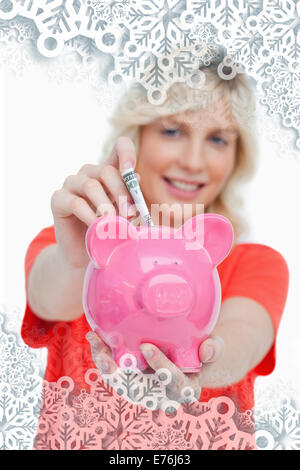 Composite image of young blonde woman putting notes into a pink piggy bank - Stock Photo