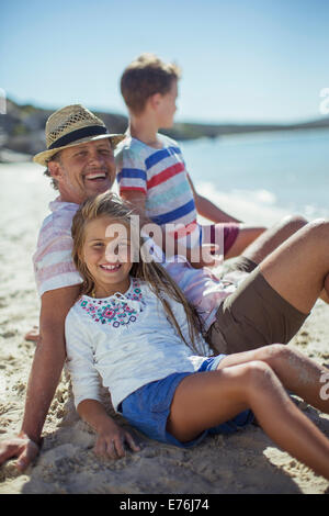 Family sitting in sand together - Stock Photo