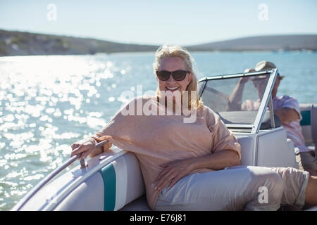 Older woman sitting in boat on water - Stock Photo