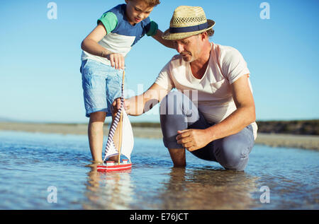 Grandfather and grandson playing with toy boat in water - Stock Photo