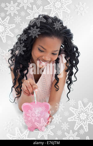 Composite image of a young girl lying on the floor putting money into a piggy bank - Stock Photo