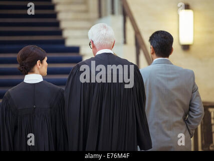 Judges and lawyer walking through courthouse together - Stock Photo