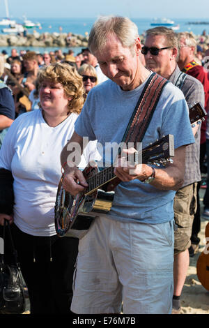 Lyme Regis, Dorset, England. A guitarist at the Guitars on the Beach event plays along with Rockin' all over the - Stock Photo