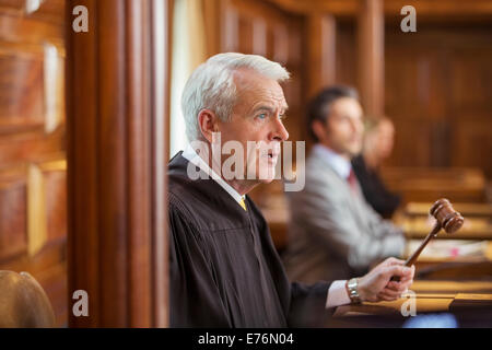 Judge banging gavel in court - Stock Photo