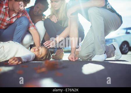 Friends examining injured girl on sidewalk - Stock Photo