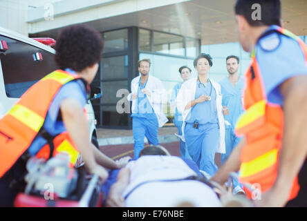 Doctors and nurses rushing to patient on ambulance stretcher - Stock Photo