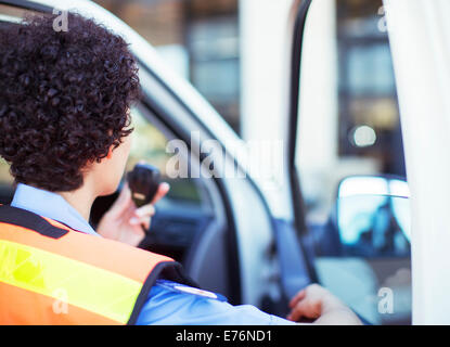 Paramedic using walkie talkie in ambulance - Stock Photo