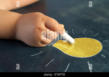 Macro close up of infant hand drawing a yellow bulb on blackboard. - Stock Photo