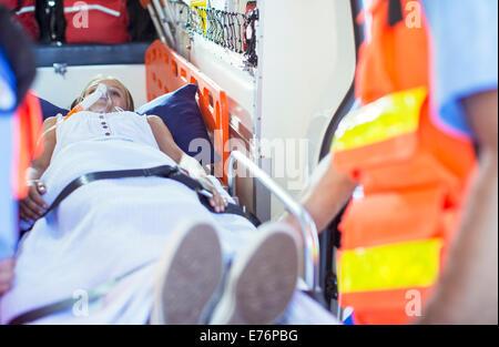Paramedics examining patient on stretcher in ambulance - Stock Photo
