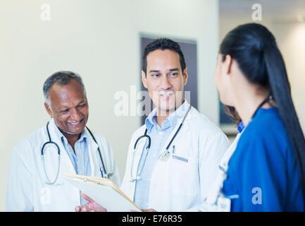Doctors and nurse talking in hospital hallway - Stock Photo