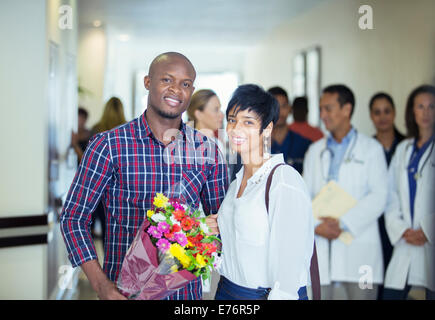 Couple carrying bouquet of flowers in hospital - Stock Photo