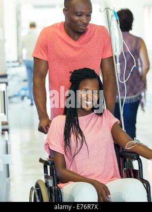 Man wheeling girlfriend in hospital hallway - Stock Photo