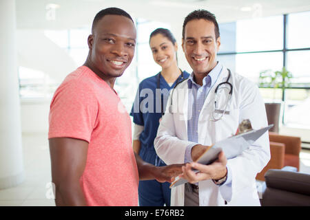 Doctor and patient smiling in hospital - Stock Photo