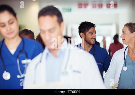 Doctors and nurses talking in hospital hallway - Stock Photo