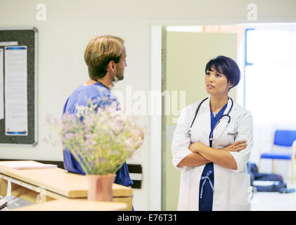 Doctor and nurse talking in hospital - Stock Photo