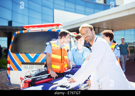 Doctor with paramedics outside hospital - Stock Photo