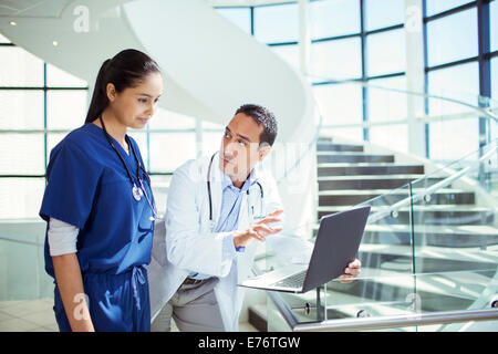 Doctor and nurse using laptop in hospital - Stock Photo