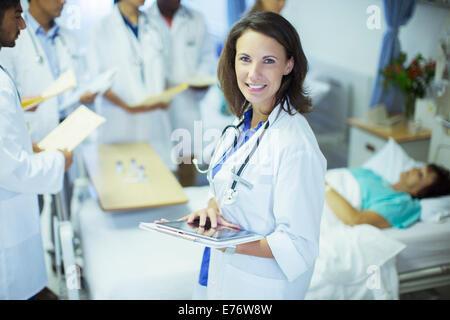 Doctor using digital tablet in hospital room - Stock Photo