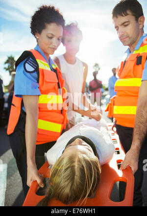 Paramedics carrying patient on stretcher - Stock Photo